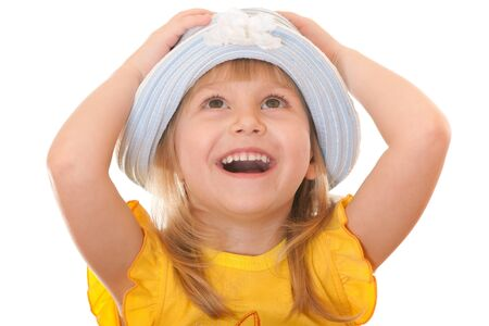 A cheerful little looking up girl in a summer hat is holding her hands on the head; isolated on the white background Stock Photo - 9133001