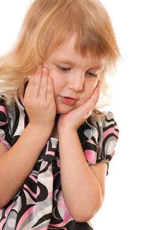 A sad little girl is holding her head with hands; isolated on the white background Stock Photo - 9133005