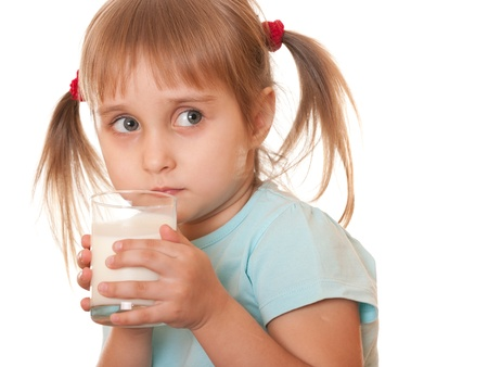 A serious girl is holding a glass of milk in her hands; isolated on the white background photo