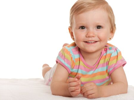 A closeup portrait of a smiling pretty little girl lying on white; isolated on the white background photo