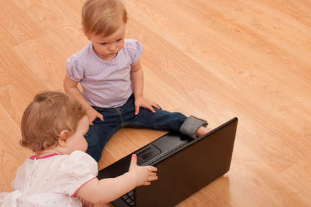 discovering: Two little girls are discovering a laptop on the floor