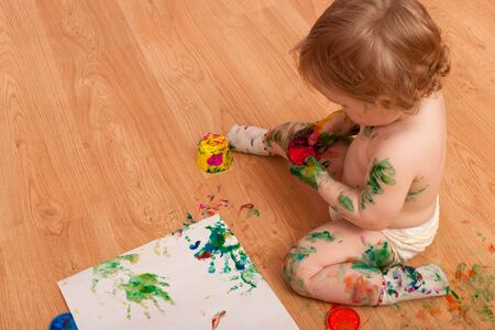A little girl sitting on the floor is playing with paints making mess all around Stock Photo - 9286077