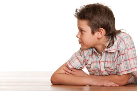 A serious boy is lying on the wooden floor; isolated on the white background Stock Photo - 9295857