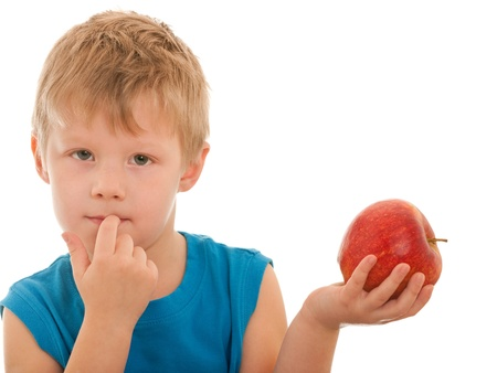 A portrait of al thoughtful blond boy holding a big red apple in his hand; isolated on the white background photo