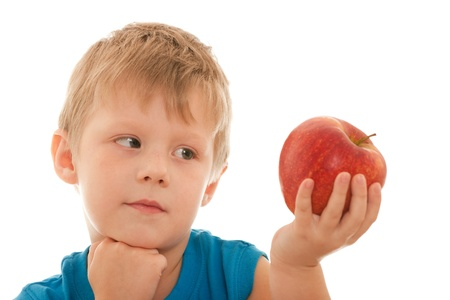 A portrait of al thoughtful boy holding a red apple in his hand; isolated on the white background photo