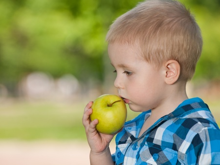 A thoughtful boy with an apple is standing in the park photo