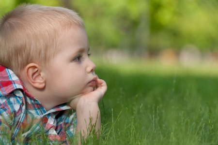 side profiles: A thoughtful little boy is lying on the green grass Stock Photo