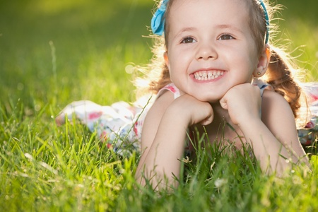 A cheerful little girl is lying on the green grass photo