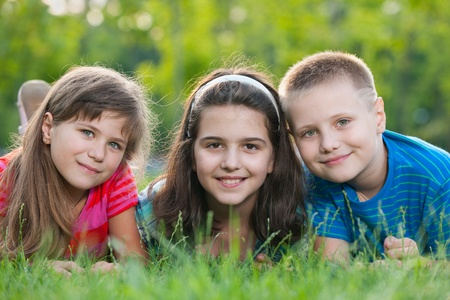 lying in front: Three lying on the grass smiling children Stock Photo