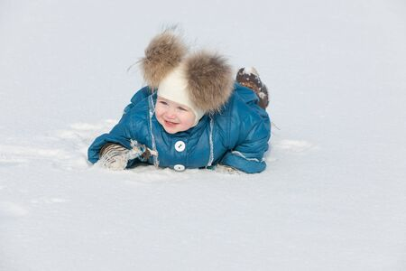 A cheerful little girl is walking in the winter park photo
