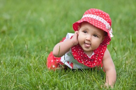 lying on grass: A pretty baby girl is playing on the grass Stock Photo