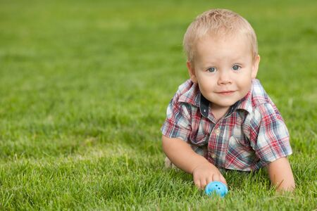 A smiling little boy is playing on the green grass photo