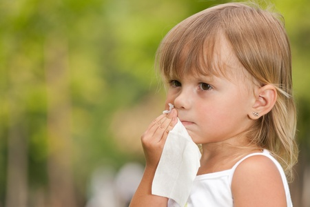 wipe: A serious little girl is wipes a mouth after meal  Stock Photo