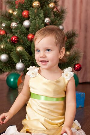 A cheerful toddler in a golden dress is smiling at the decorated New Year tree photo