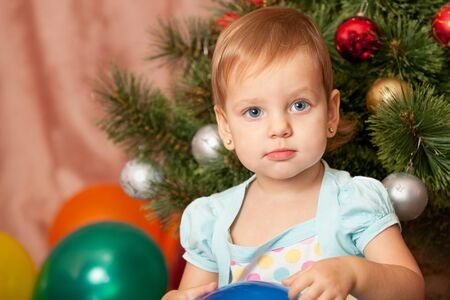 A portrait of a serious little girl with big grey eyes at the christmas tree Stock Photo - 10277631