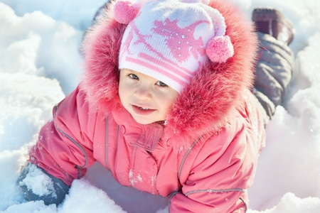 A smiling little girl in pink is lying in the snow Stock Photo - 10277669