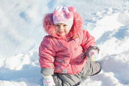 A cheerful little girl in pink is walking in the winter park photo