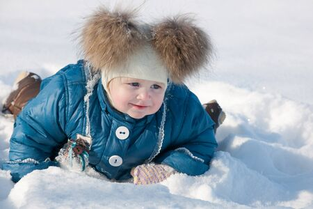 A cheerful little girl in blue is crawling in the snow while walking in the winter park photo