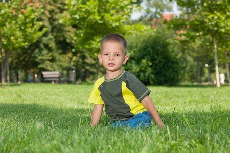 Un niño pequeño serio sentado en la hierba verde