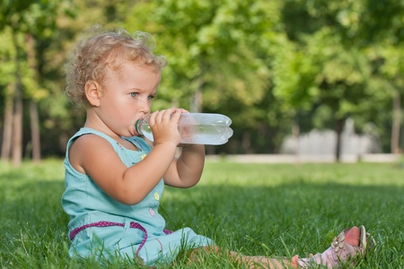 drink bottle:  A little girl is drinking water outdoors Stock Photo