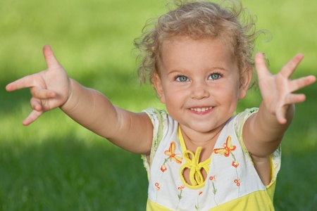 A cheerful little girl stretching hands forward is sitting on the green grass in the park photo