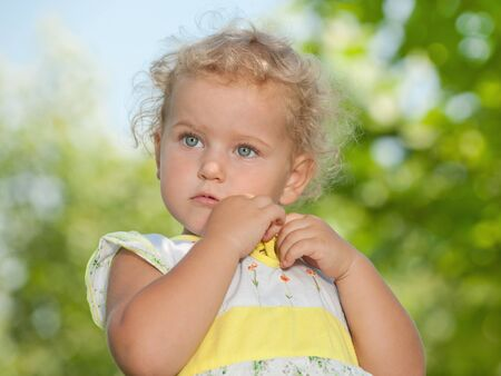 A portrait of a little sad pretty girl with blonde curly hair in the summer park  photo