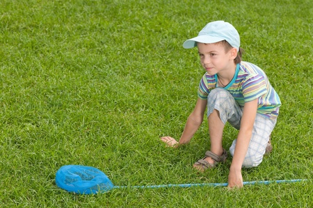 butterfly net: A boy with a butterfly net is sitting on the summer lawn  Stock Photo