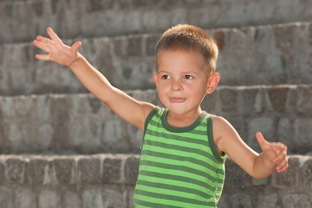 one story: A boy in a casual vest is telling a story showing its monster in front of stone stairs Stock Photo