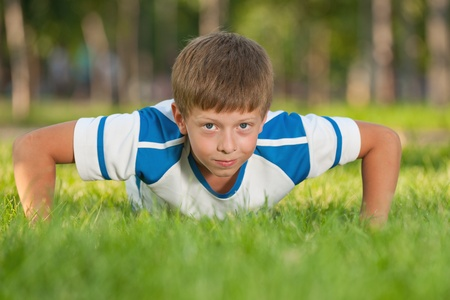 A handsome athletic boy is pushing up on the green meadow Stock Photo - 10277626