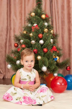 A nice toddler is sitting at the decorated christmas tree photo