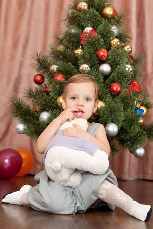 A pretty cheerful little girl is holding a toy at the decorated christmas tree photo