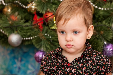A portrait of a serious little girl at the christmas tree photo