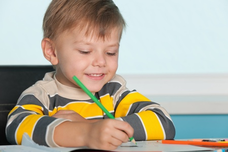 A little smiling boy draws at the desk photo
