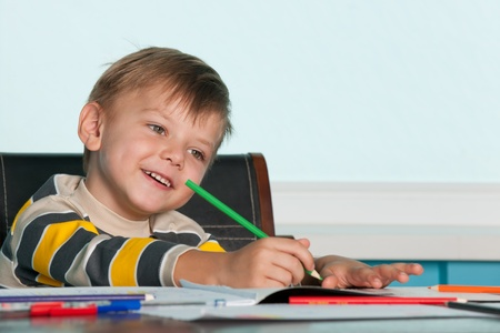 drawing table: A smiling drawing little boy is sitting at the table
