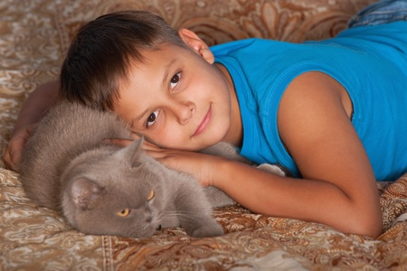 A smiling boy is hugging his cat photo