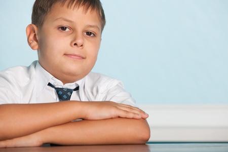 diligente: Un muchacho diligente está sentado en el escritorio
