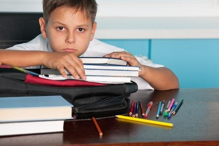 homework student: A sad boy is sitting at the desk Stock Photo