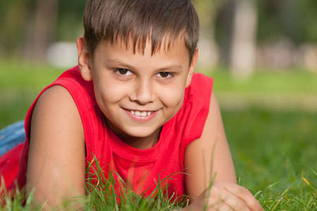 A cheerful smiling boy in red is lying on the green grass Stock Photo - 10864852