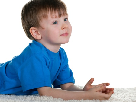 A smiling boy is lying on the carpet; isolated on the white background photo