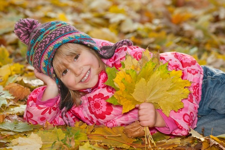 A lying little girl is holding yellow leaves in autumn photo