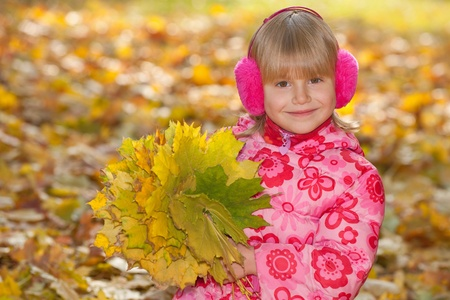 A portrait of a smiling little girl with yellow leaves in autumn photo