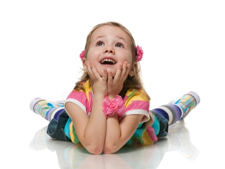 A smiling little girl is looking up; isolated on the white background photo