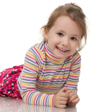 A smiling little girl in striped sweater; isolated on the white background photo