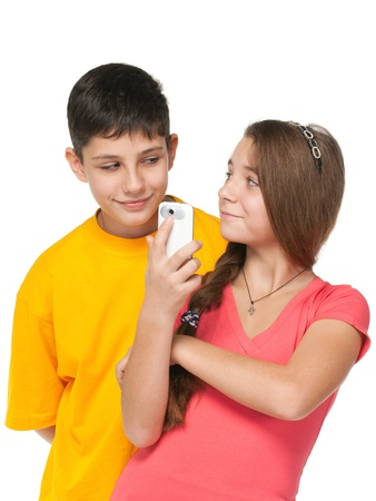 A portrait of happy kids with a cell phone; isolated on the white background photo