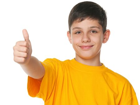 A smiling teenager shows his thumb up; isolated on the white background photo