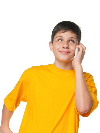 A portrait of a boy in yellow shirt with a cell phone; isolated on the white background photo