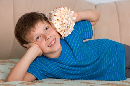 A handsome smiling boy is listening to the shell Reklamní fotografie