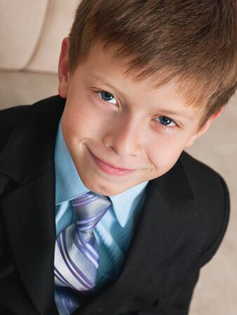 A portrait of a cheerful boy in black suit photo