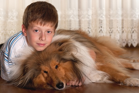 A lying on the floor serious boy is hugging his dog photo