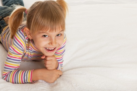 bedspread: A smiling little girl is lying on the bedspread; isolated on the white background